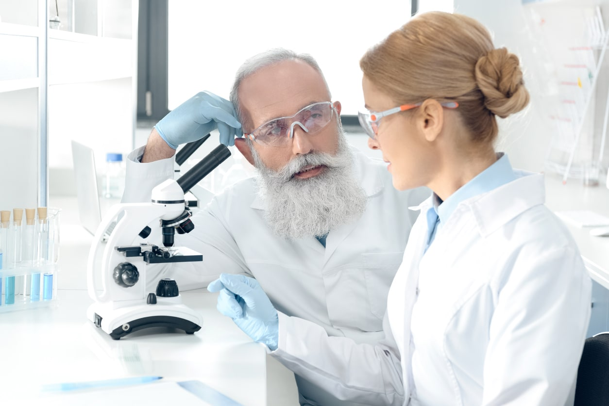 Mature scientists working in laboratory looking at each other